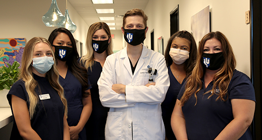 Dr. Dathan Hamann and the Saguaro Dermatology Team smiling for a group photo in their Phoenix office